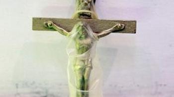 Un condón en el crucifijo